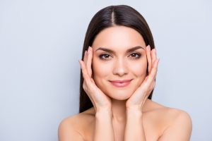 Woman with healthy skin holding her face