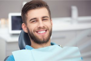 Male sitting in dentist chair smiling