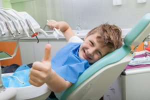 Kid sitting in chair with thumbs up