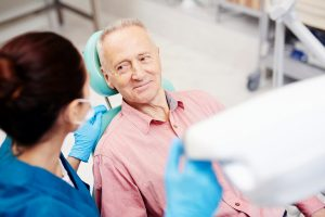 Senior man sitting in dentist chair smiling