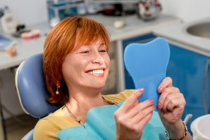 Smiling senior woman new dental implants