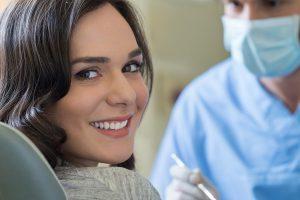 Woman smiling in dental chair before teeth cleaning