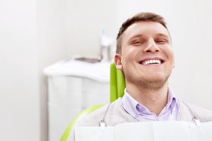 White male smiling in a dentist chair