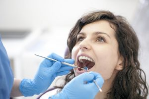 Beautiful woman with dentist doing dental work
