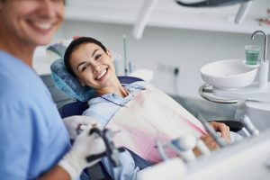 Woman smiling in dentist chair laid back
